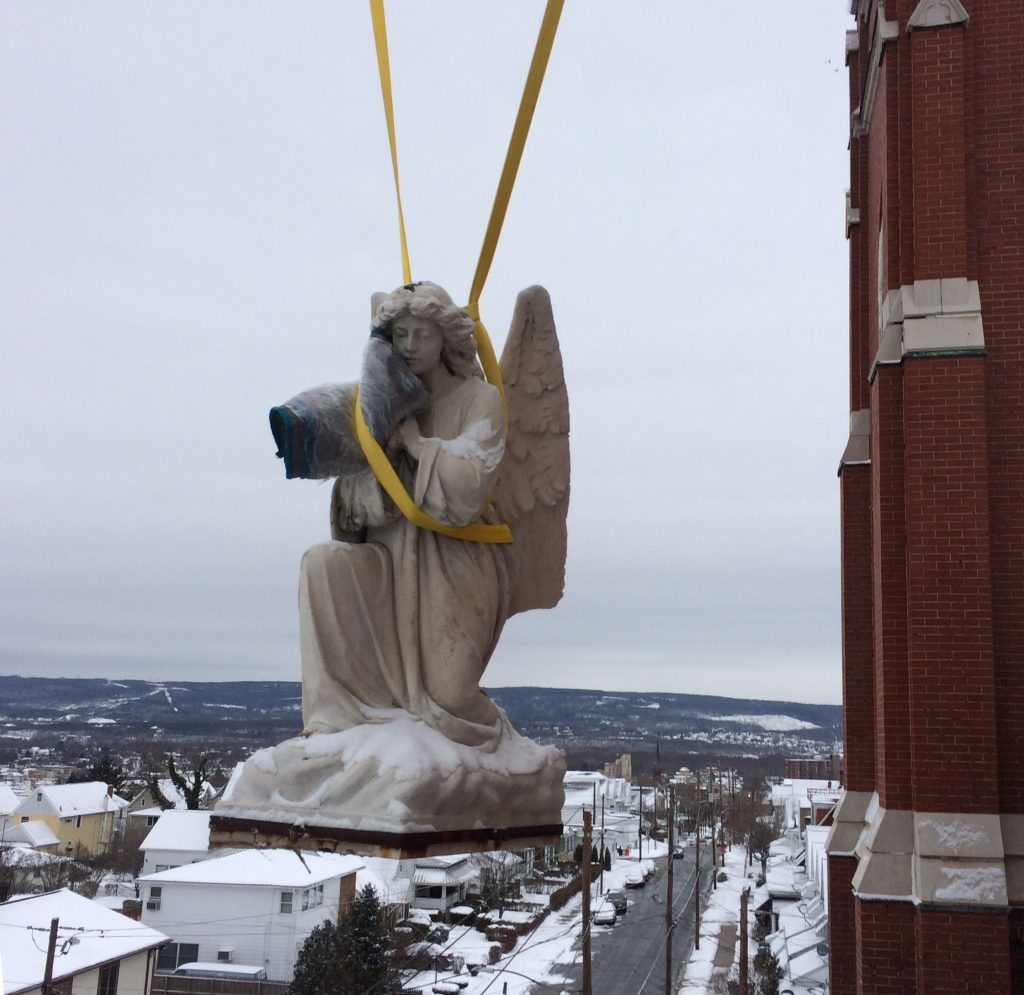 Hand-carved 100 year old kneeling angel gently lowered from above the high entryway