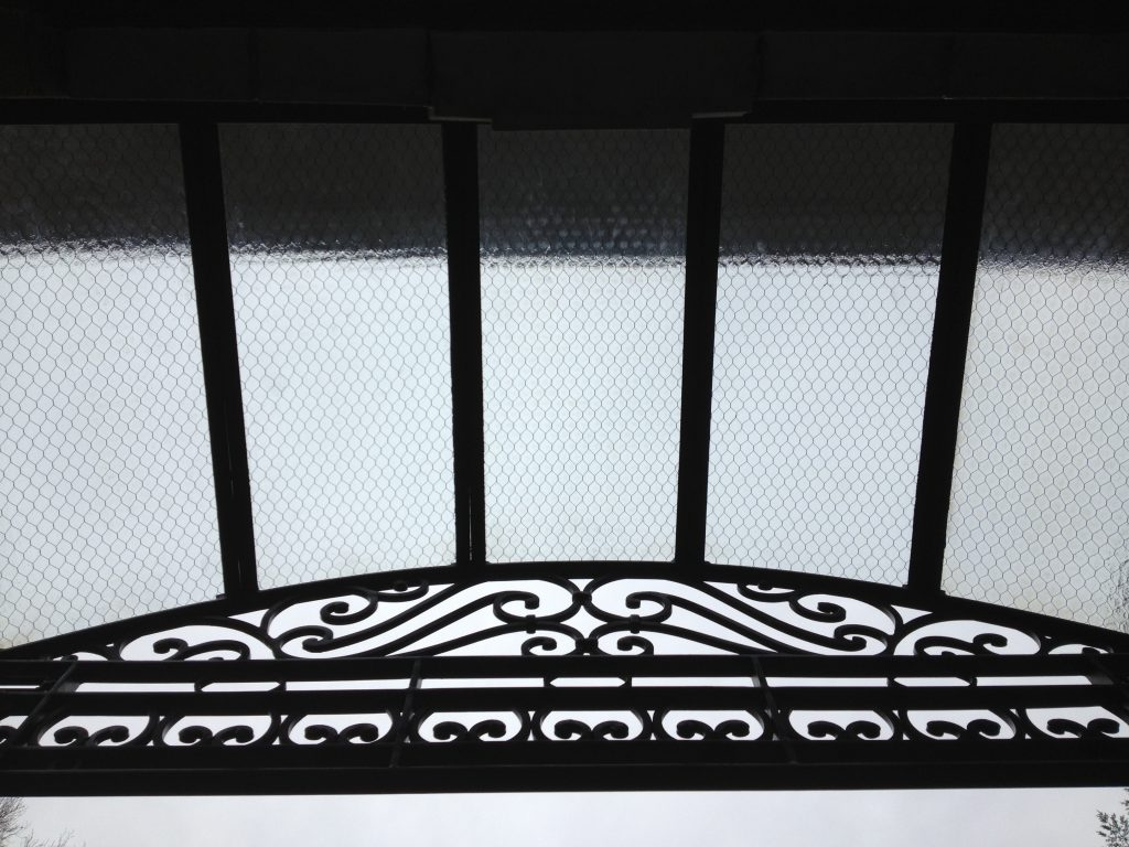 Vintage hammered chicken wire glass was used in this hand-fabricated iron awning
