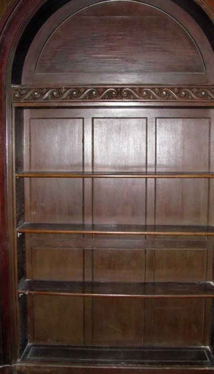 Carved wooden built in shelving unit with decorative top