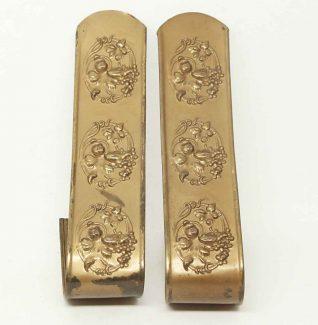 pair of pressed brass tie backs
